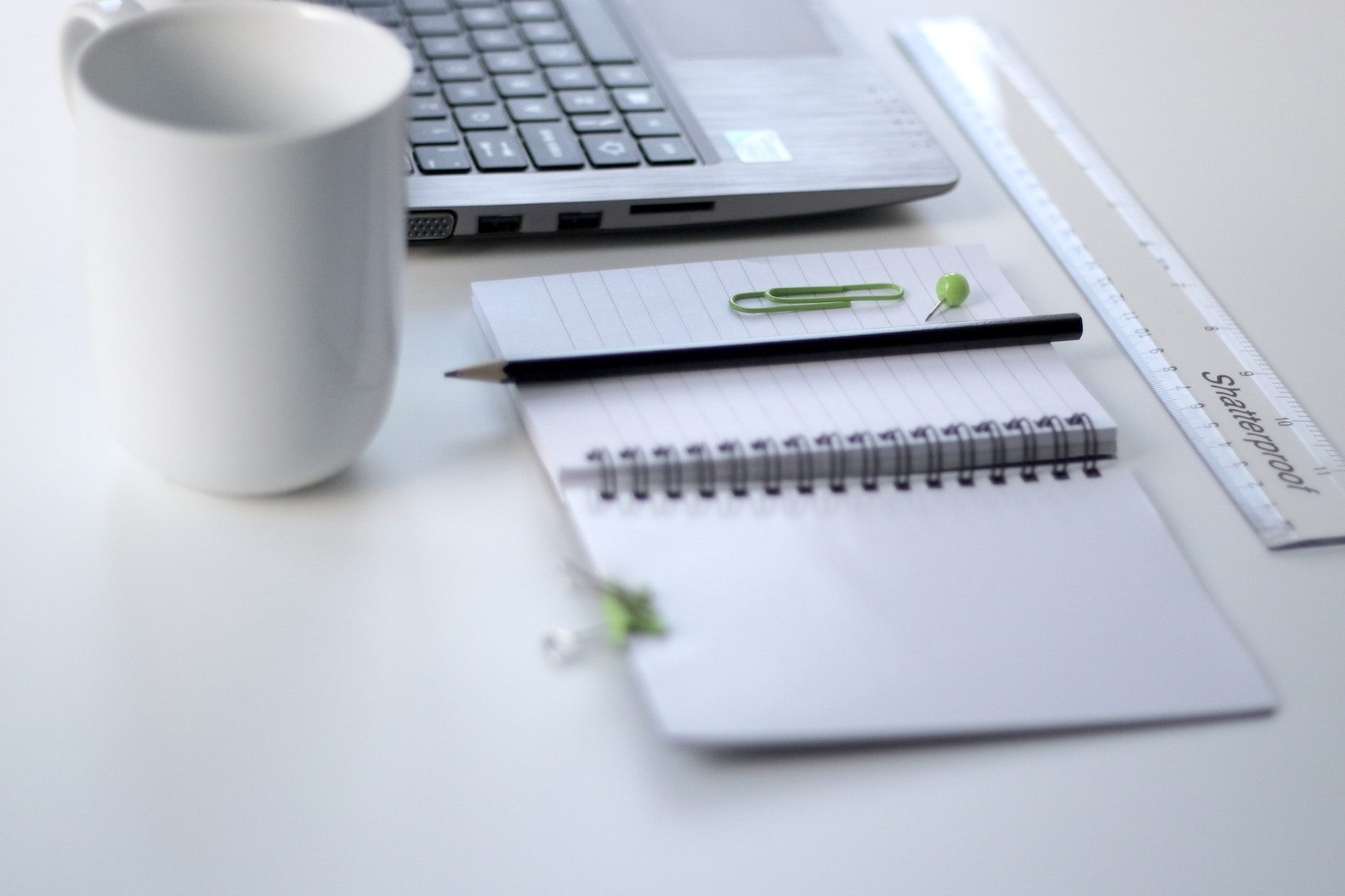 A coffee cup, notebook, ruler and computer are part of a podcast studio