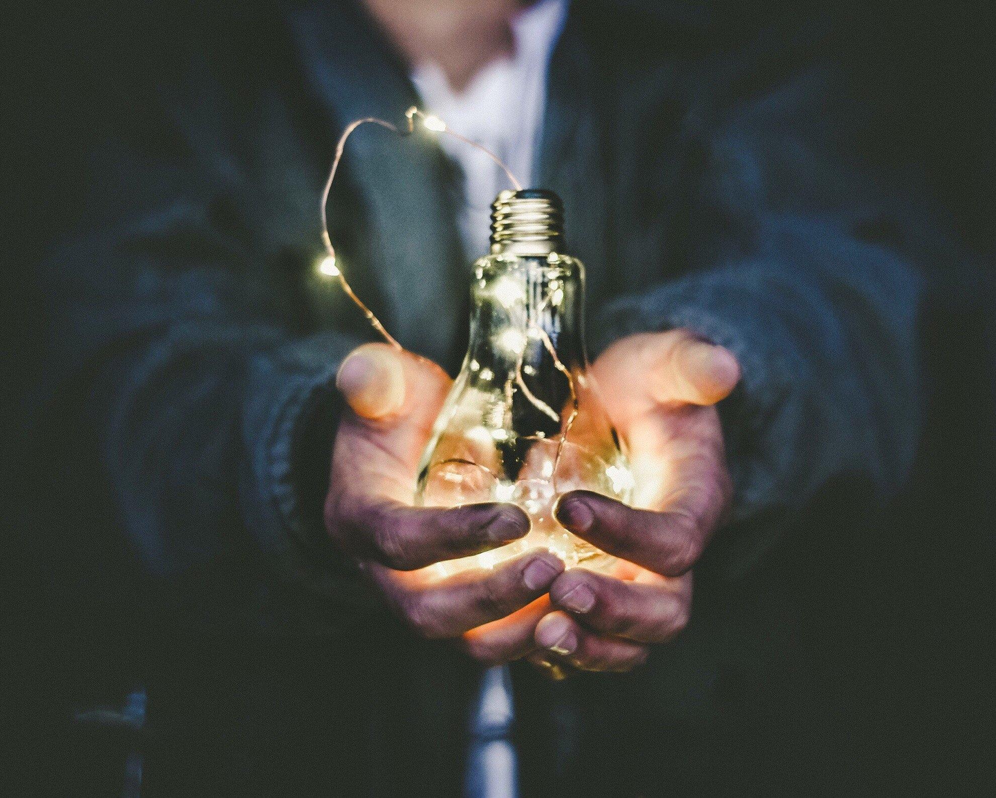 hands holding illuminated lightbulb in a dark room