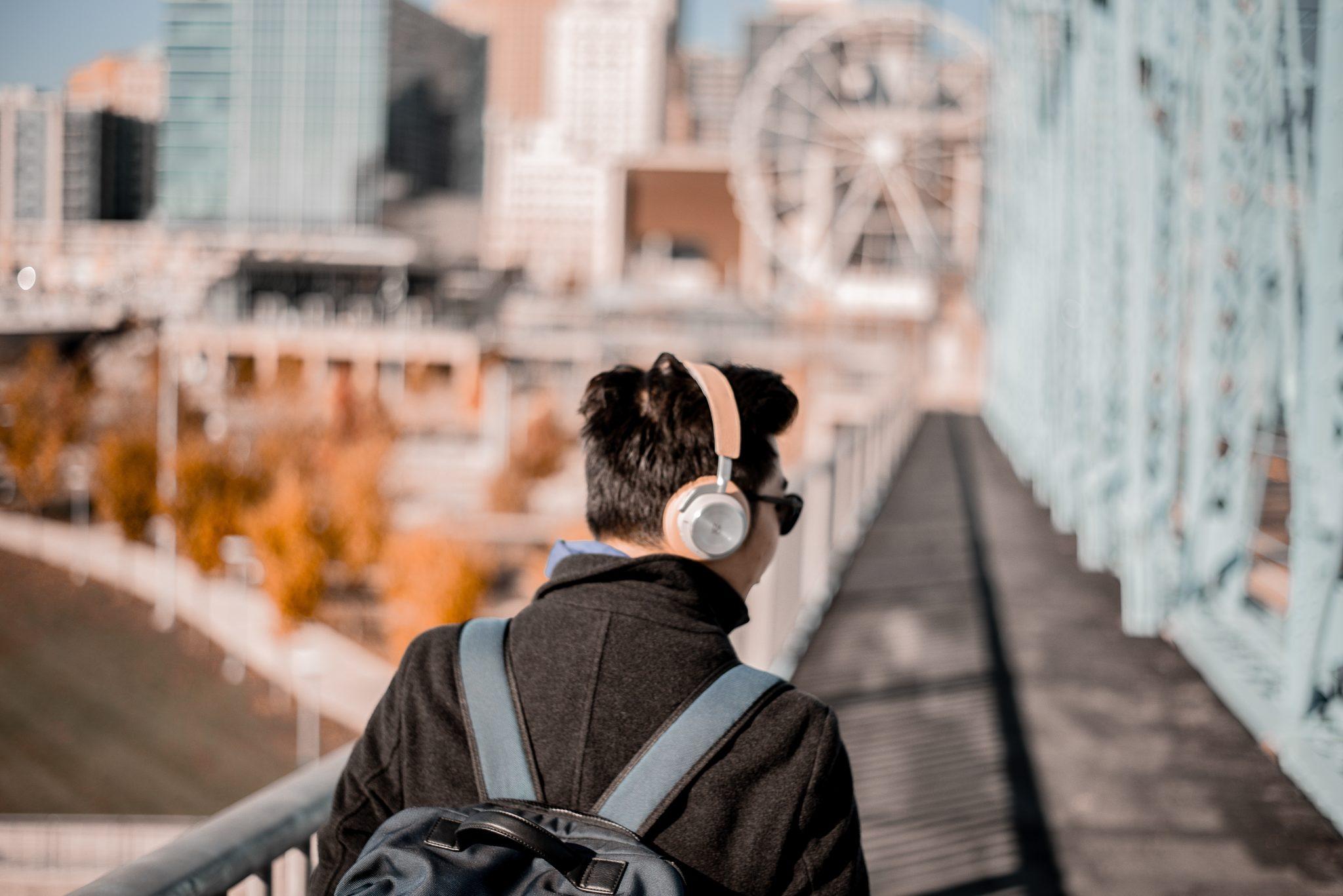 Man wearing headphones while walking toward a city