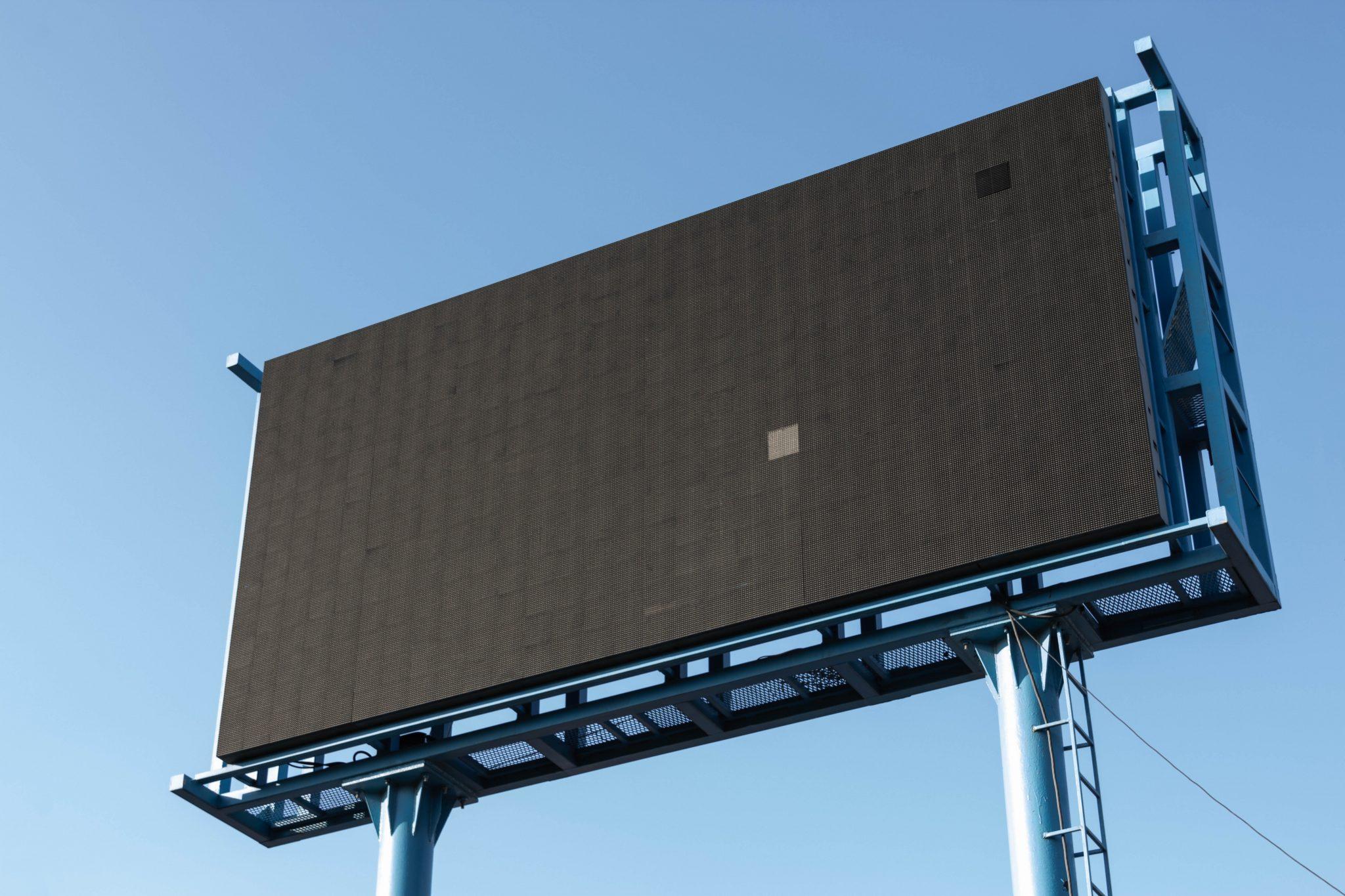 A blank, black billboard in front of a blue sky